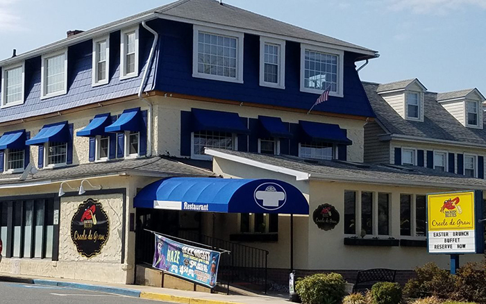 Large three story restaurant with beige paint and blue window awnings.