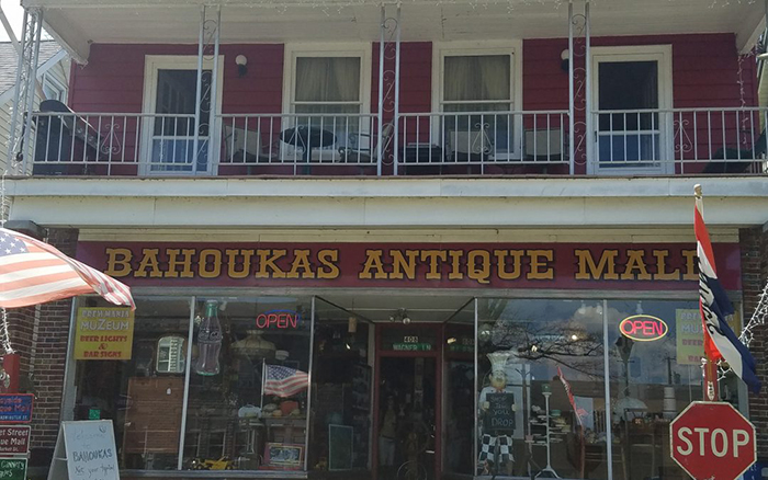 Two story red antique shop building with white windows and second story porch