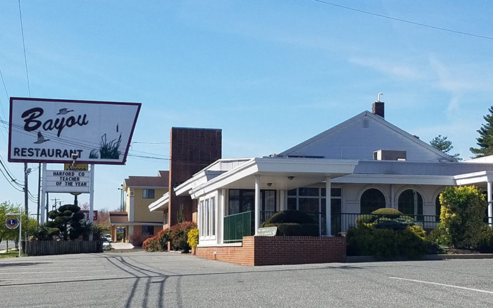 Parking Lot view of a large white restaurant with brick trim and a large sign outfront.