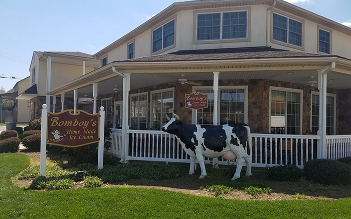 Corner view of large ice cream shop with a ceramic cow out front.