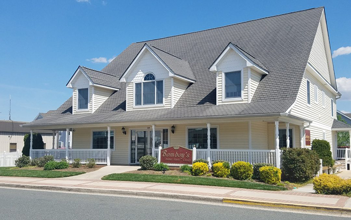 Front street view of large yellow homesyle building with dormer windows and wrap around porch.