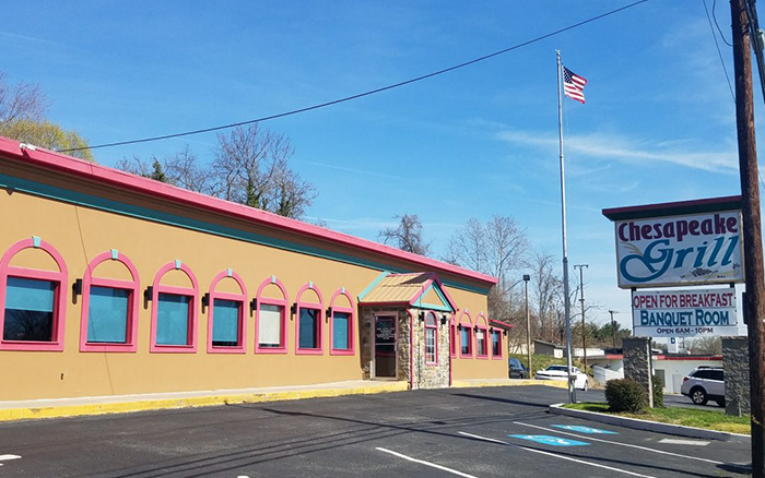 Parking lot view of long tan building with red trim and large sign outfront.