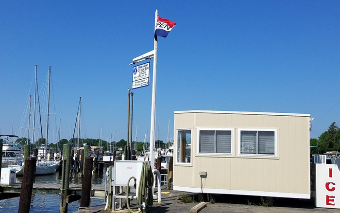 Boat Marina with a boat house and and open flag on a pole.