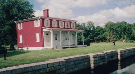 Waterfront view of a historic red building with white windows and white porch on green grass.