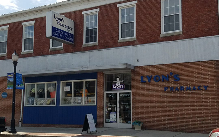 Pharmacy front brick building with blue accents and signage