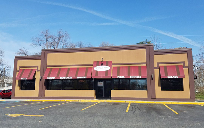 Parking lot view of tan pizza shop with red and brown stripped awnings.