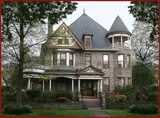 Victorian style grey stone mansion with red trim windows and wrap around porch