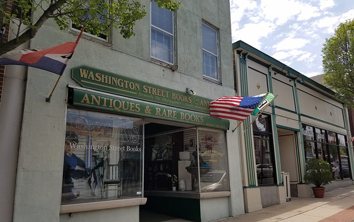 Two story paved city storefront with green banners and flags.