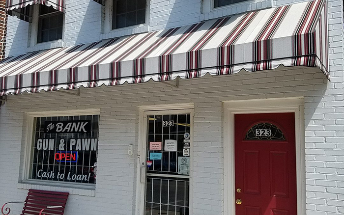 White brick storefront with white and red striped awning.