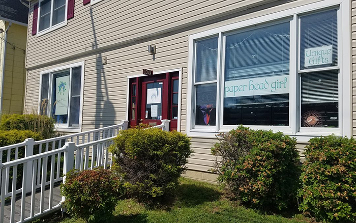 Tan building with red door and ramp entry with a sign in the window reading paper bead girl