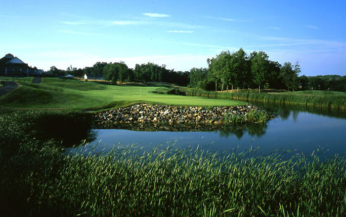 View of serene golf course with pond.