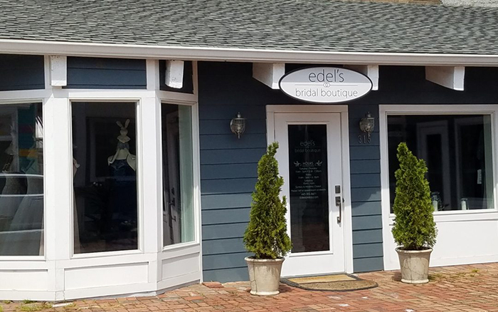 Storefront view of a blue and white bridal boutique with brick paving.