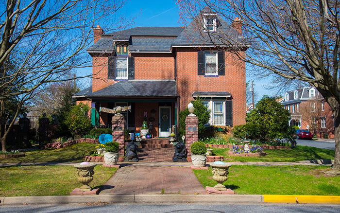 Two Story brick house with black roof and shutters