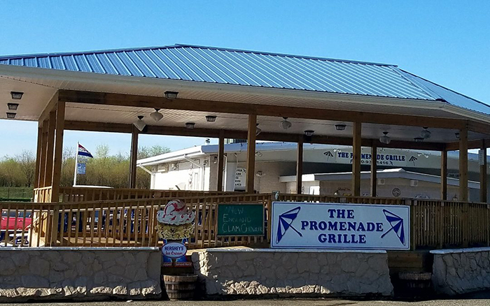 Outdoor wooden covered dining deck with sign that reads The Promenade Grille